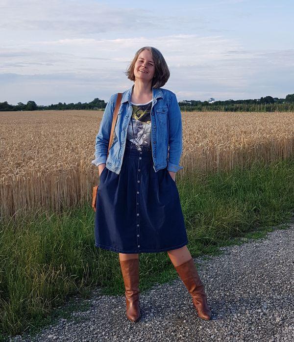 Kühler Sommerabend mit Midijeansrock in dunkelblauer Waschung, mit Knopfleiste, auf der Hüfte getragen und mit heller Jeansjacke kombiniert.