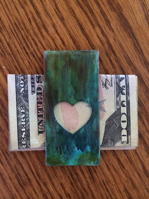 Money clip with a heart cut out. Green patina