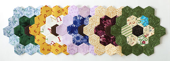 Five multi-coloted overlapping hexagon flower blocks in a row on a white background.