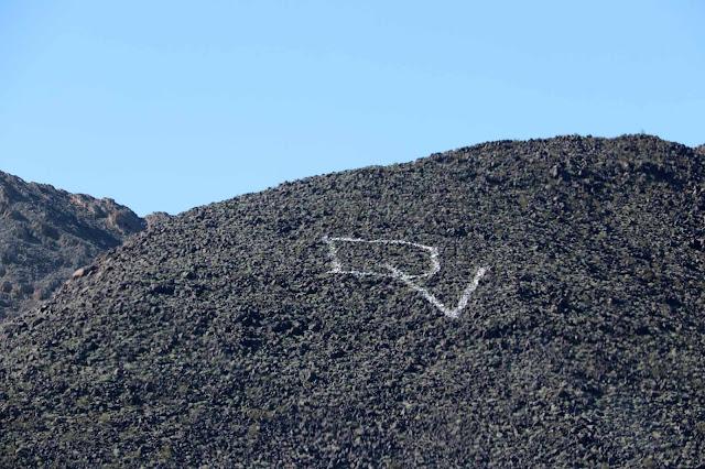 Vuoren rinteeseen taiteiltu teksti DV