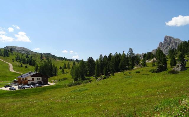 Grüne Wiesen, Hügel, Hotel mit Autos und Spielburg am Falzaregopass, Südtirol