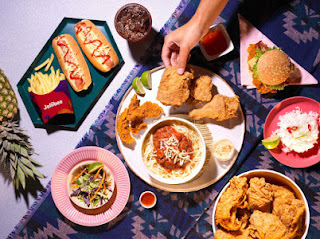 A selection of white circular plates, and red rectangular boxes with Jollibee in white font with an animated bee on the front of them containing pieces of different food such as golden brown chicken and a hotdog on a white circular table on a bright background