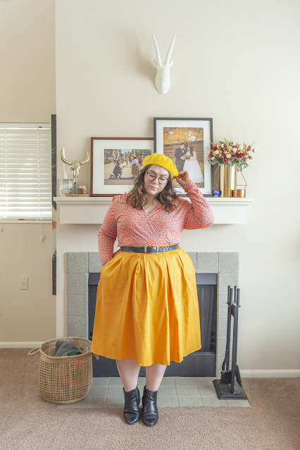 An outfit consisting of a yellow beret, a pink long sleeve wrap dress and a yellow midi skirt and black chelsea boots.