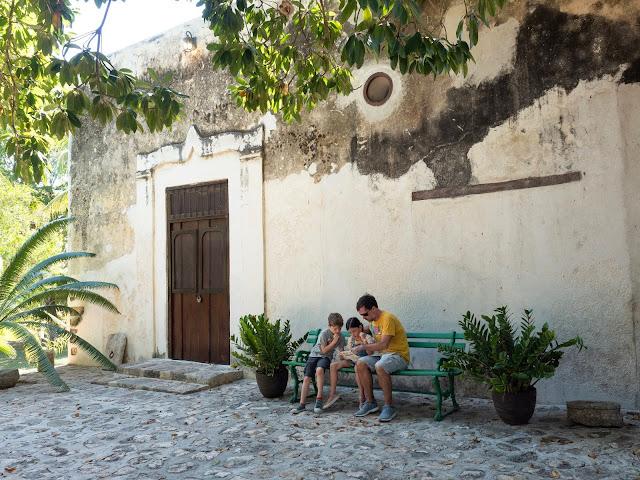 Hombre y niños sentados en un banco en un jardín colonial