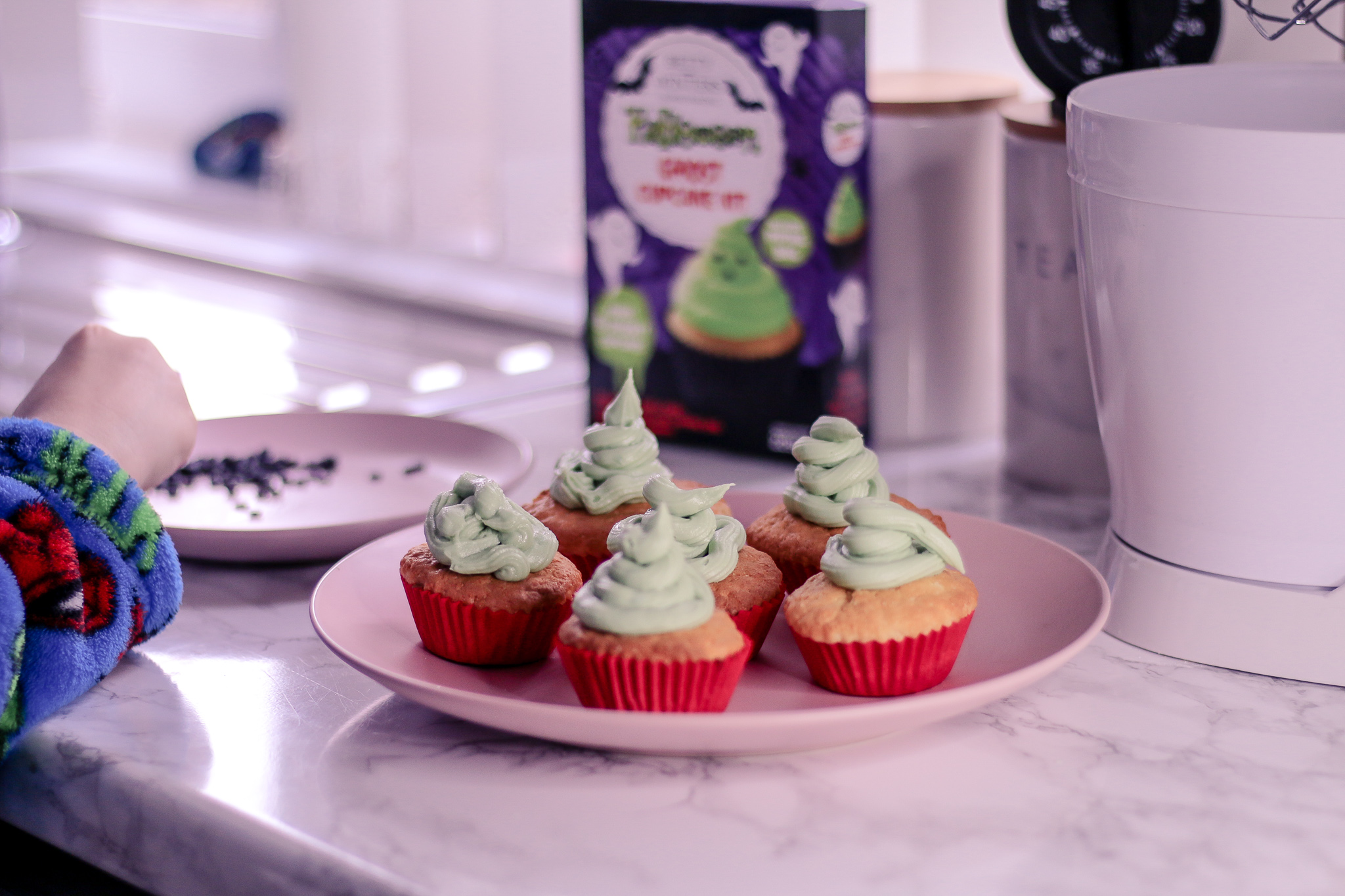 Close up photo of 6 cupcakes with green icing on a pink plate on top of a white marble kitchen worktop