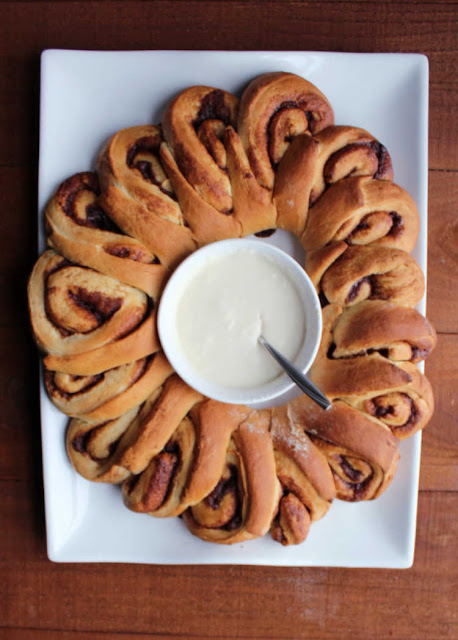 freshly baked cinnamon roll wreath with bowl of icing in the middle
