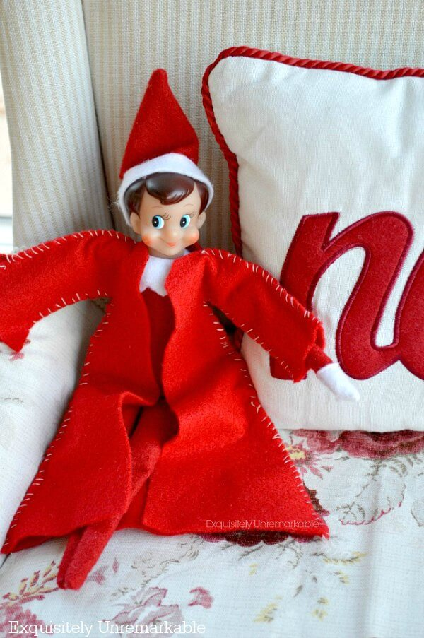 Elf on the shelf with a DIY coat sitting on chair with Christmas pillow