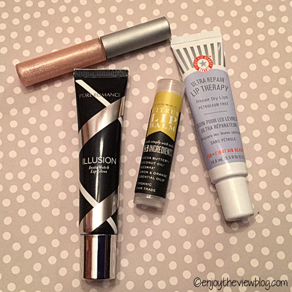 lip products lying on a tan and white polka dot surface