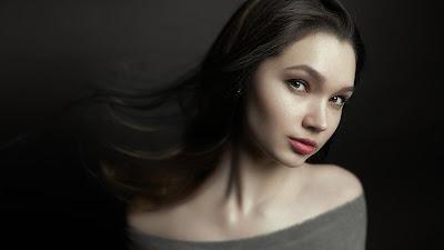 Bonita chica con fondo dark mirando fijamente a cámara