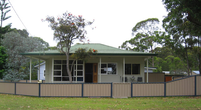 The house now has a low beige 'colourbond' galvanised iron fence with grey-blue fence posts and rails. The home now has a veranda covering the front porch. The front door is widened and modernised. An extension has been build on the right hand side. The home has been re-roofed with forest green corrugated iron and the walls repainted in a pale green with white window trim.