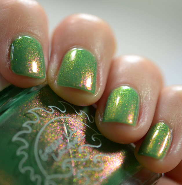 green nail polish with red and green shimmer swatched on white person's nails