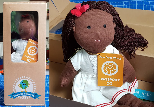 One Dear World ethnic doll dark skin and curly hair sitting in packaging box
