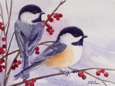 Two chickadees sit in a berry bush in winter