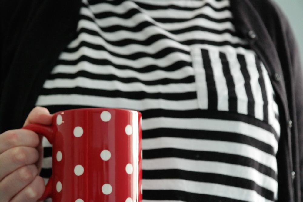 Red spotty mug, black and white stripy tee.