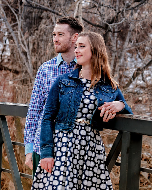 a young couple poses on a bridge for a photo during their engagement session at Eben G Fine Park in Boulder Colorado