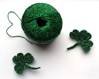Above-view of skein of metallic green yarn, flanked by two completed shamrocks.