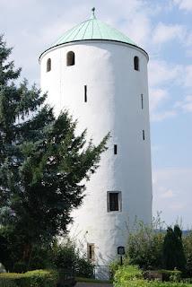 Ein runder, weißer Turm mit türkisfarbenem Stotzdach