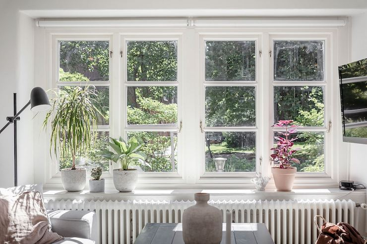 Gran ventanal de pequeño salón decorado en tonos naturales