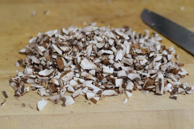 Mushrooms finely chopped on a cutting board with a knife to the side.