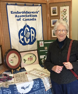 a woman poses in front of an Embroiderers' Association of Canada display