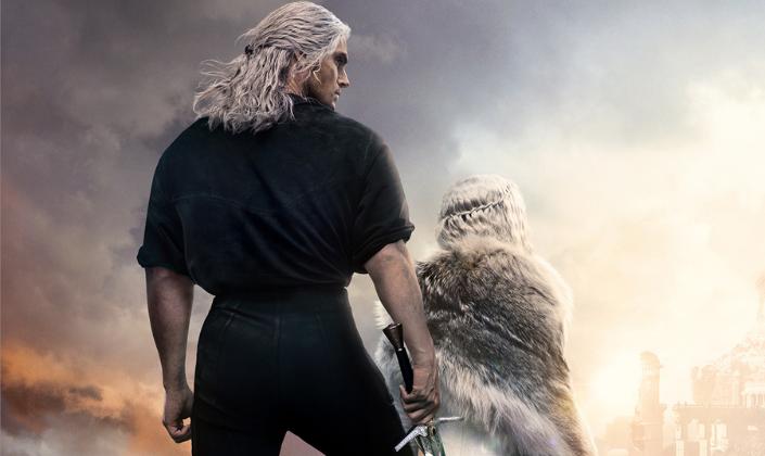 Imagem: fundo comum céu brilhante em que se vê nuvens e do outro lado um castelo nas montanhas. Em pé em um monte vemos Geralt, de costas e olhando para o lado, interpretado por Henry Cavill, vestindo preto, botas e segurando uma espada, os cabelos brancos amarrados até o ombro e Ciri, uma garota loira, de costas, com um manto de pele e um vestido branco.
