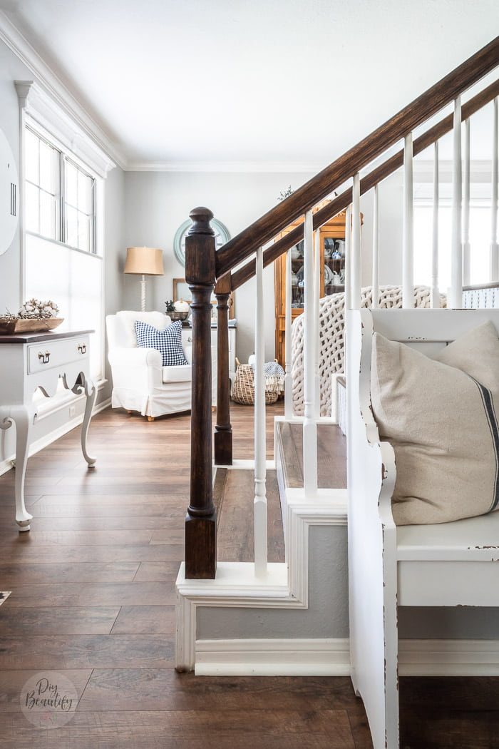 entryway with painted table, staircase, neutral furniture, pine hutch and blue Fall accessories