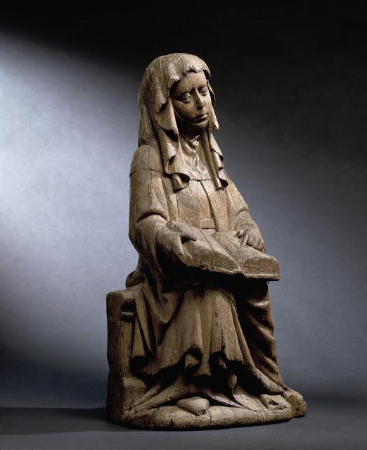 Keskiaikainen puuveistos, joka esittää istuvaa naista avoin kirja sylissään.