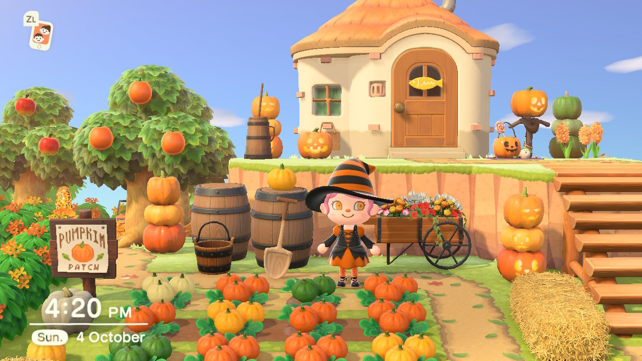 A screen shot of a pumpkin garden I made on my island in the game Animal Crossing New Horizons. The screen shot shows a garden with pumpkin patch with different coloured pumpkins, with fruit trees, barrels, spades, hay bales and pumpkin furniture behind and beside it. The garden is surrounded by green and orange hedges, and in the centre is a character dressed as a witch with pink hair and orange eyes. Her outfit is orange and black, and she's standing in front of a wooden flower cart. To the right of her are wooden steps leading up to a beige house with a brown door that is surrounded by pumpkins for Halloween.