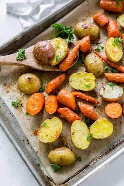 Top view of oven roasted potatoes and carrots on a baking sheet with parchment paper.