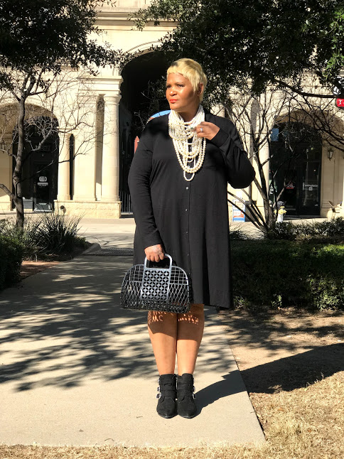 Tangie Bell is sharing how she wears pearls, boots and handbag with a solid black shirt dress