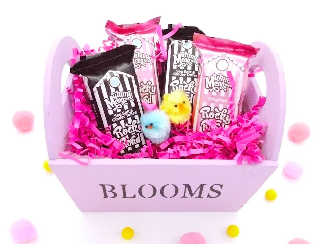 bars of mummy meagz sea salt and cinder toffee tocky road in black and white striped packaging, and original in pink and white, arranged in a lilac basket with pink shredded paper and Easter chicks