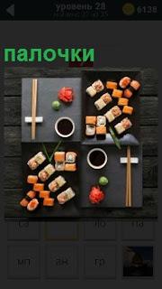 На столе приготовлено блюдо суши для двоих и положены палочки, которыми их едят