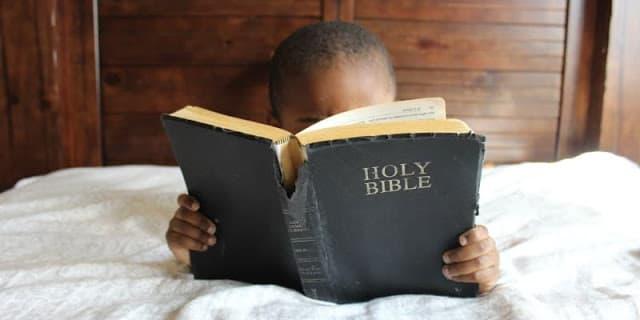 A imagem mostra uma criança negra lendo a bíblia
