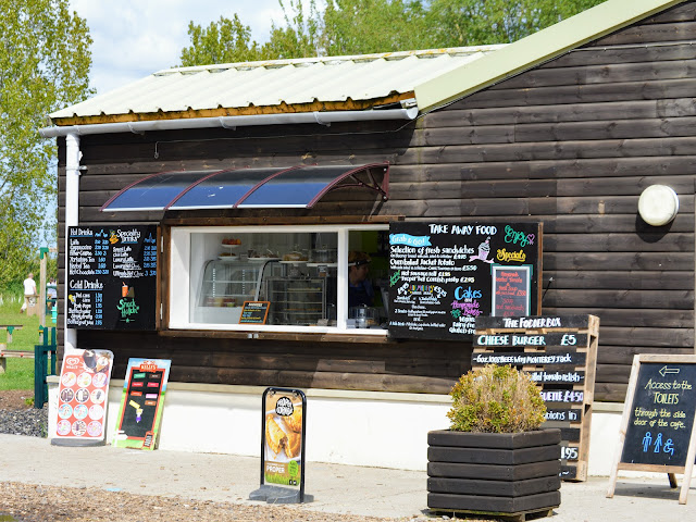 Image taken at Tattershall Farm Park of the outside of the cafe which has a hatch serving hot food, drinks and ice cream. There are menus dispalyed on chalk boards outside and inside the hatch you can see a small display which houses cakes and sandwiches.