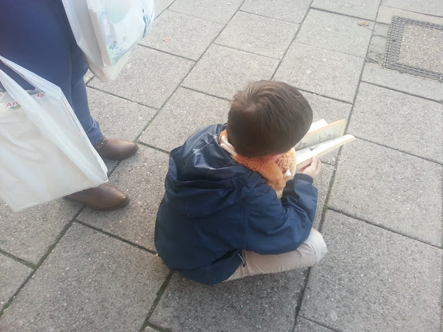 Child Seated on Pavement Reading