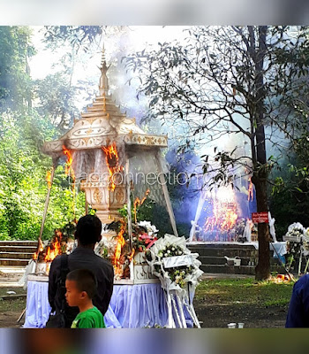 A double cremation taking place at a Lao Buddhist temple