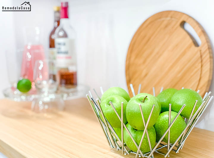 modern metal fruit bowl full of green apples