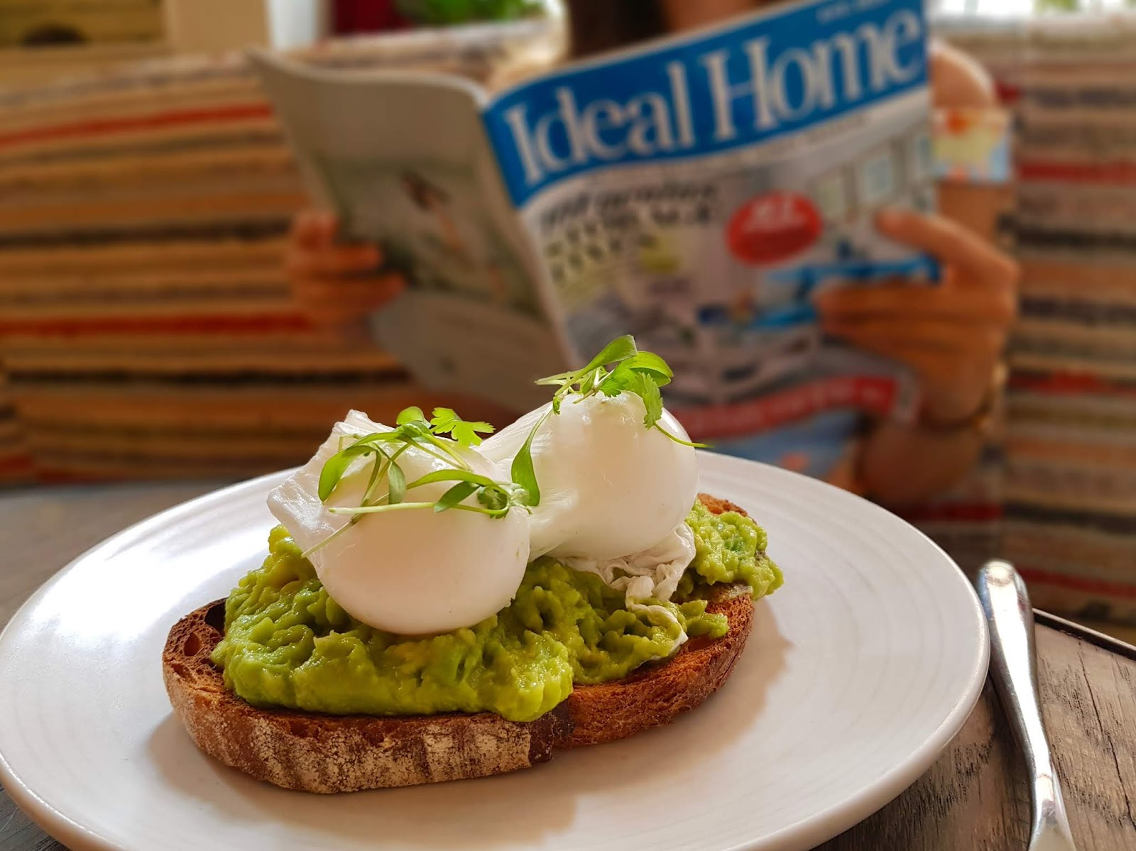plate of avocado on toast in foreground, young woman reading property magazine in background