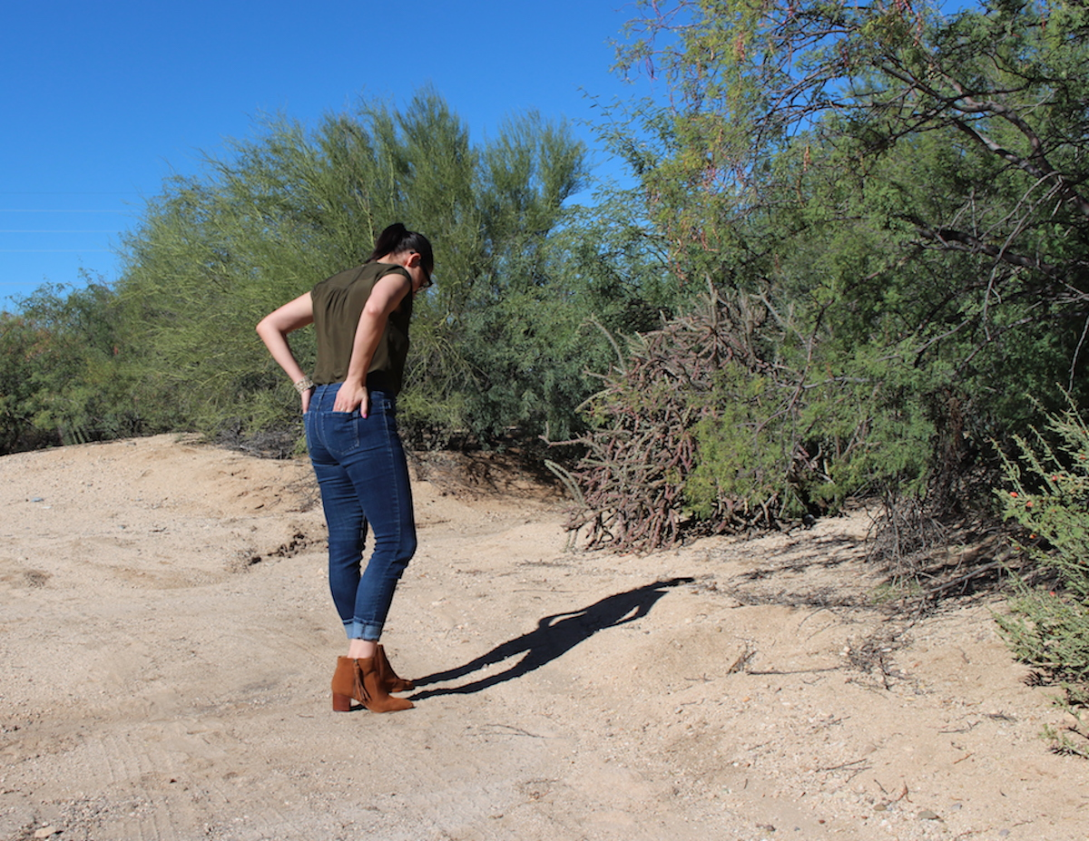 In this back shot of me wearing a silk blouse, jeans, and booties, I am looking down at the dirt in the desert.