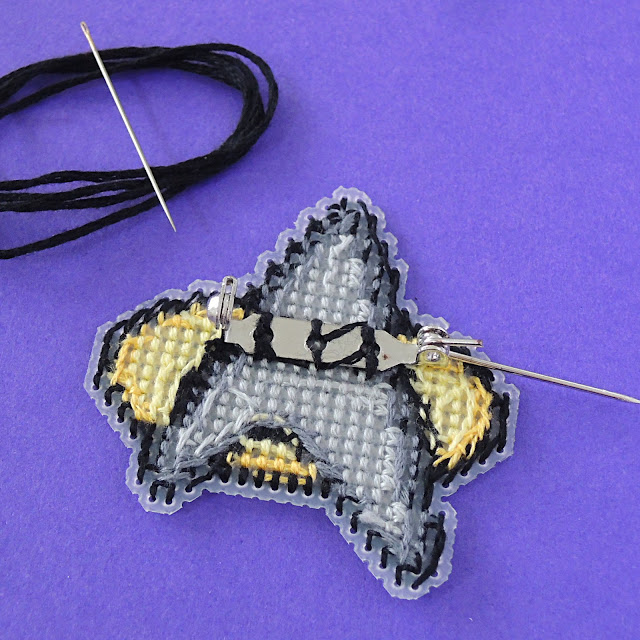 Sewing the brooch back onto plastic canvas