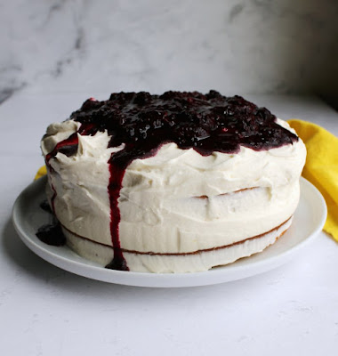 whole blackberry cake with lots of fluffy white frosting on top, barely frosted sides and some blackberry sauce dripping over the edge