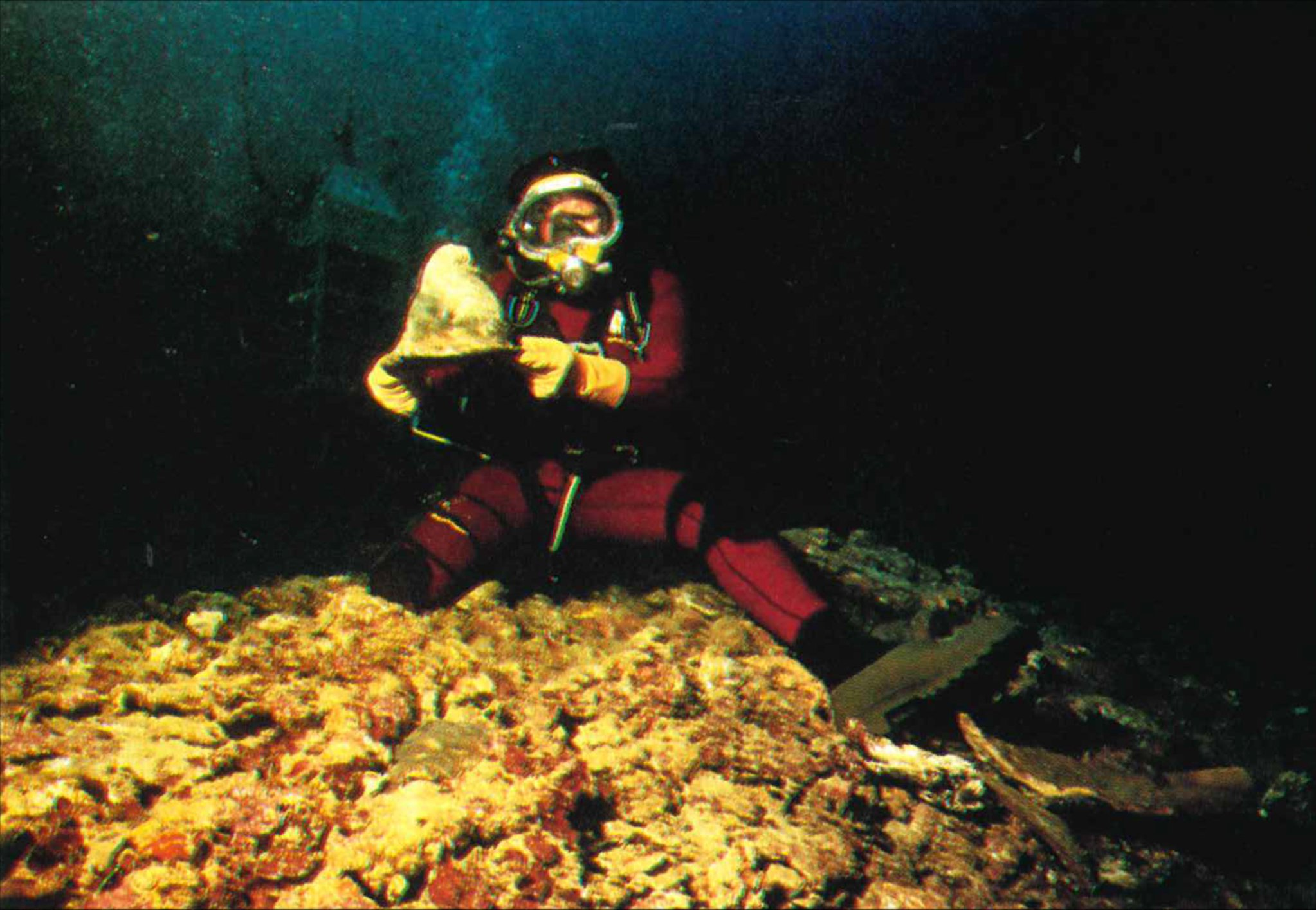A diver holding an artifact on siting on top of stone ballasts mound at the San Diego shipwreck site