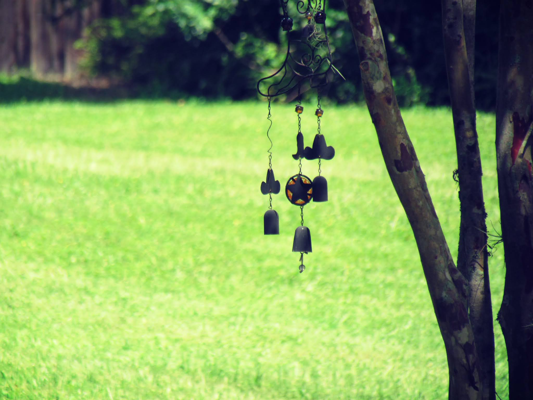 a whimsical wind chime with stars and cloud shapes blowing in the warm summer breeze in a Florida cemetery