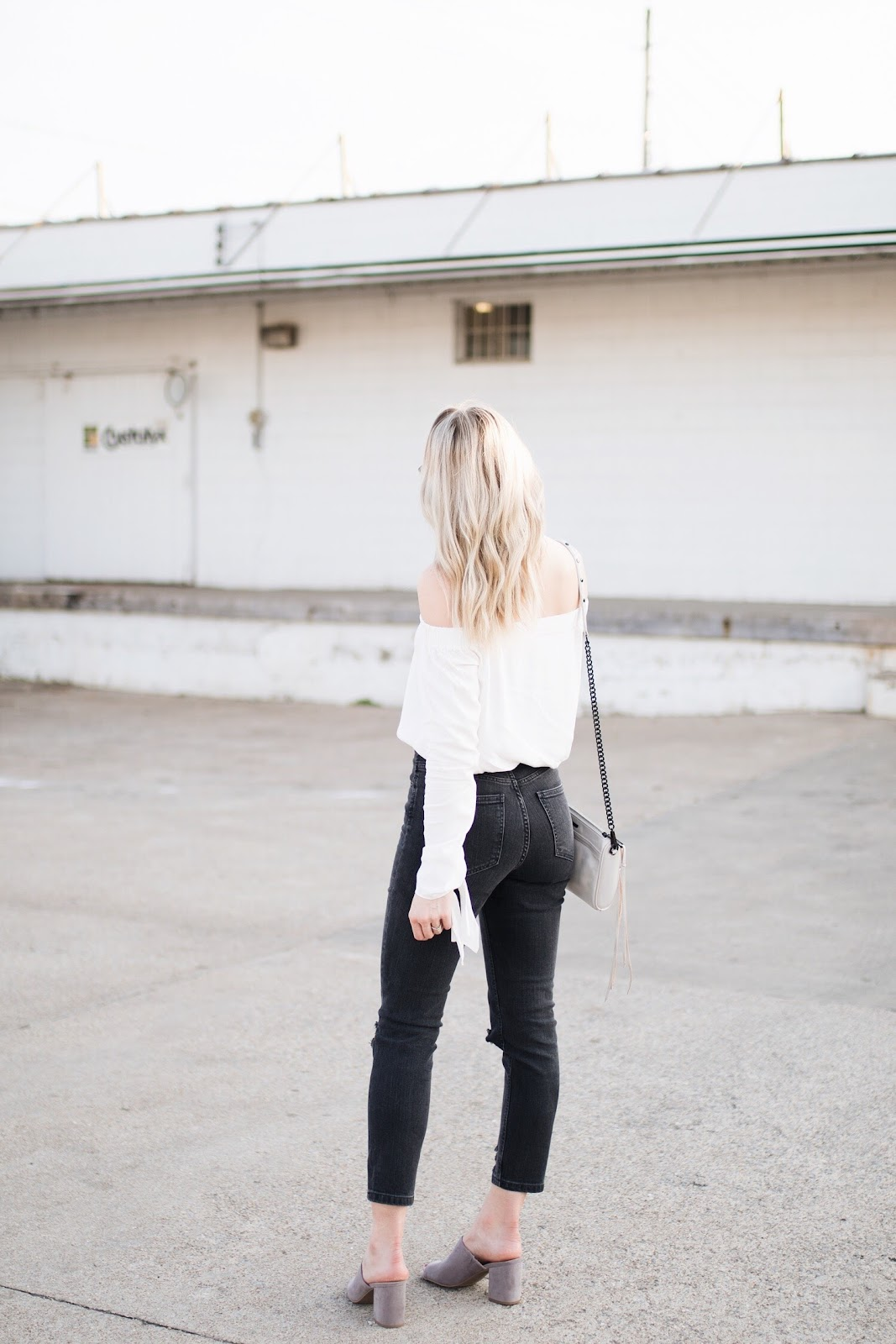 white off-shoulder top, black mom jeans