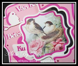 Een close-up van het swinggedeelte van de achterkant van de kaart met 2 vogeltjes in/op een nestje. A close-up of the swing part of the back of the card with 2 birds in/on a nest.