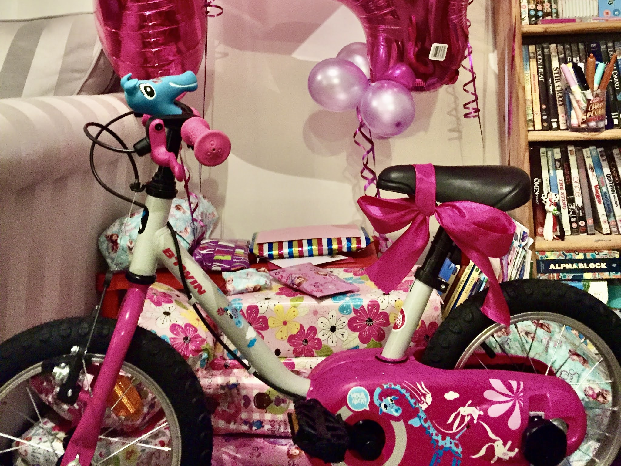 a pile of presents and balloons for a 4th birthday with a bike at the front