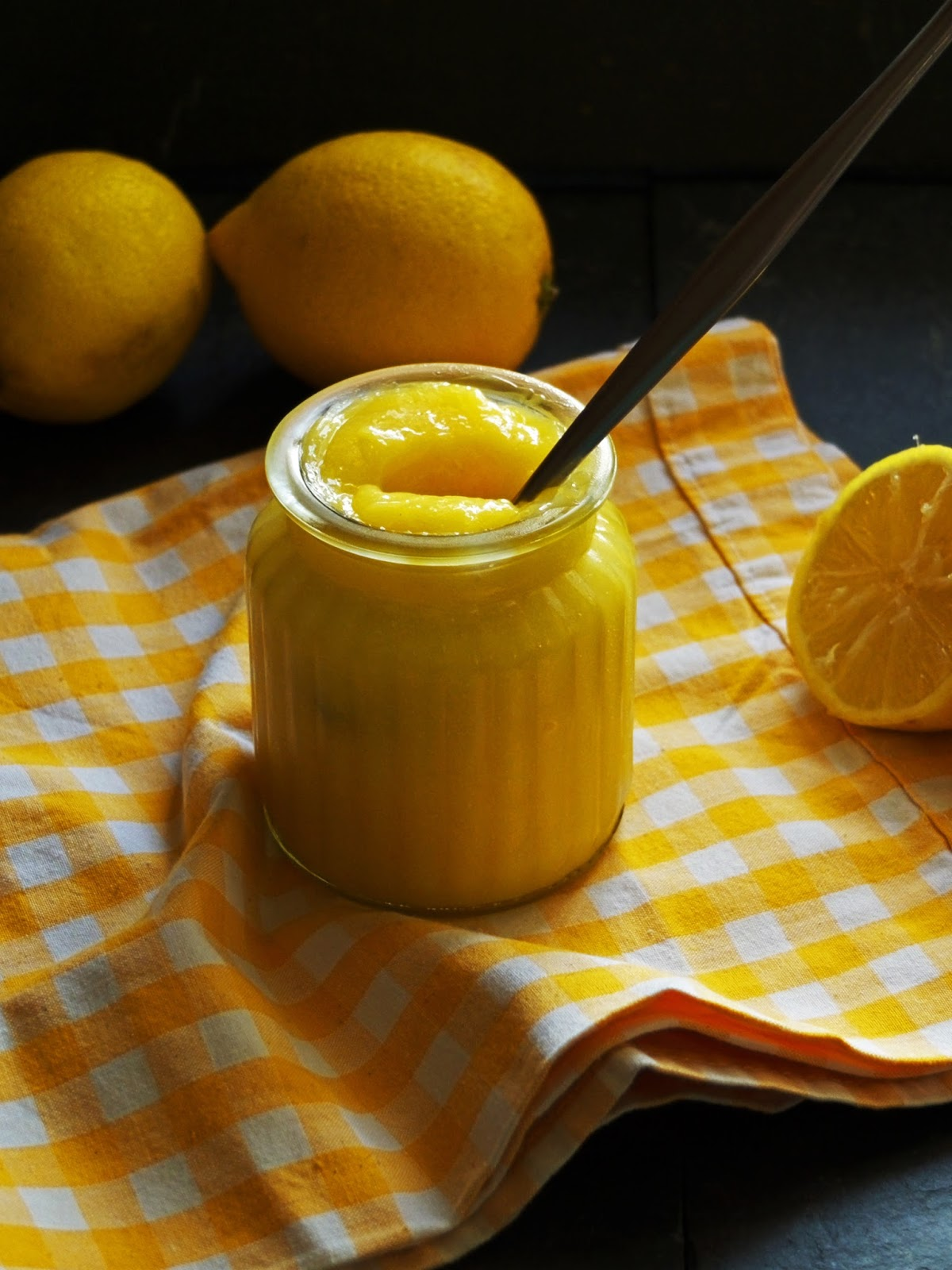 Jar of lemon curd with a spoon inside sitting on a checkered yellow tea towel.