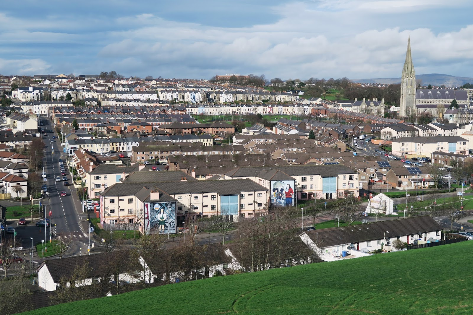 Looking down from the medieval Derry city walls over the Bogside which is a residential area with many murals on the sides of houses