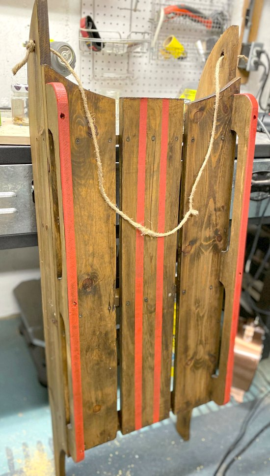 Red striped lines on a wooden stained sled