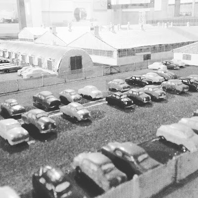 Model of a factory. In the foreground are lines of cars parked outside it.